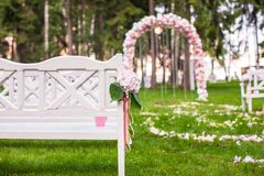 Wedding benches and flower arch for ceremony. Wedding benches and flower arch for a wedding ceremony outdoors Royalty Free Stock Photos