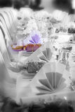 Wedding or birthday table setting, colour emphasis. A wedding or birthday table setting with colour removed and isolated around one napkin and bonbon (cracker) Royalty Free Stock Photo