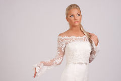 Wedding blouse. Young beautiful and graceful girl in a wedding dress with a neckline and a lace blouse with a gray background royalty free stock images