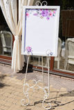 Wedding board on the white forged stand with a guest list Royalty Free Stock Photo