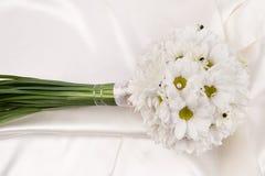 Wedding boquet. White flowee wedding bouquet arrangement on white silk background Royalty Free Stock Images