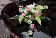 Wedding boquet on expensive car cowl. Wedding boquet on expensive black car cowl stock photography