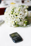 Wedding bouquet. With the phone lying on the banquet table Royalty Free Stock Photography