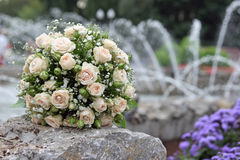 Wedding bouquet. The beautiful beige bouquet of the bride lays on a fountain parapet Royalty Free Stock Photo