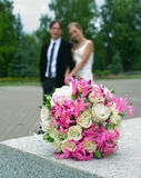 Wedding bouquet. Against young couple. Shallow DOF Stock Image