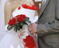 Wedding bouquet. From red roses at the bride in hands Stock Photos