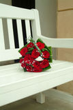 Wedding bouquet. Of red roses on the white bench Royalty Free Stock Photography