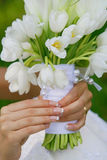 Wedding Bouquet. Beautiful wedding bouquet in gentle hands of the bride royalty free stock image