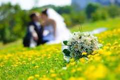 Wedding bouquet. Bridal bouquet of white roses on a green meadow and blurred newlyweds Royalty Free Stock Image