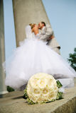Wedding bouquet. Bridal bouquet of white roses and blurred newlyweds at background Royalty Free Stock Photography