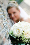 Wedding bouquet. Bridal bouquet of white roses and blurred bride near the wall at background Royalty Free Stock Photography