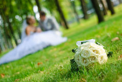 Wedding bouquet. Bridal bouquet of white roses on a green meadow and blurred newlyweds Stock Images