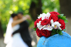 Wedding Bouquet. A shot of a wedding bouquet with the bride and groom hugging all blurred out in the background Stock Image