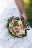 Wedding bouquet. Close-up of pink and white roses wedding bouquet in bride's hand with part of bride's body in picture on a green grassy background Stock Image