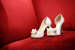 Wedding shoes. On a red sofa Stock Photos