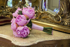 Wedding bouquet. Of pink peony flowers on antique dressing table with mirror Stock Photo