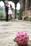 Wedding bouquet. In focus and couple in the background Royalty Free Stock Image