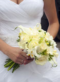 Wedding bouquet. Close-up of  white roses wedding bouquet in a hands of a slim bride in a white wedding dress Stock Photos