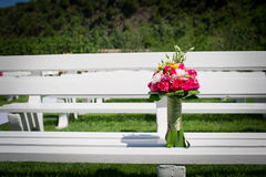 Wedding bouquet. The wedding holding flowers on a white bench Royalty Free Stock Photography