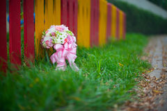 Wedding bouquet. Bouquet of wedding holding flowers on the fence side of the grass Stock Images