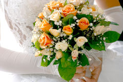 Wedding bouquet. Wedding bouqet from white and orange roses in bride's hands stock photography