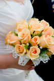 Wedding bouquet. From orange roses in bride's hands stock photo