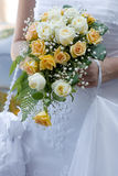 Wedding bouquet. Wedding bouqet from white and yellow roses in bride's hands royalty free stock photography