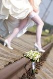 Wedding bouquet. On the rails on the backgroud of bride's legs Royalty Free Stock Image
