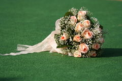 Wedding bouquet. The beautiful bouquet of roses lays on a grass Royalty Free Stock Photo