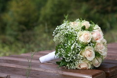 Wedding bouquet. The wedding bouquet of light roses is on a bench Royalty Free Stock Image