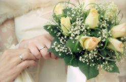 Wedding bouquet. And hands of married couple in soft focus Stock Photo