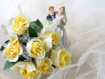Wedding Bouquet. Bride and groom figurine, bouquet of yellow roses (artificial) on white netting royalty free stock photos
