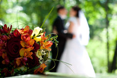 Wedding Bouquet. A wedding bouquet with the bride and groom in the out of focus background Stock Photos