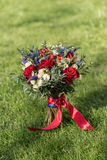 Wedding bouquet, against the background of grass. A wedding bouquet of red and white roses, against a background of green grass Royalty Free Stock Image