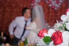 Wedding bouquet against wedding. The groom kisses the bride. A wedding bouquet in the foreground Stock Images