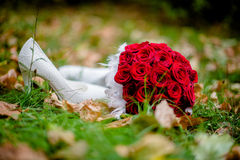 Wedding bouquet on the autumn leaves. Wedding bouquet of red roses in the autumn leaves Stock Photos