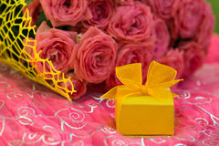 Wedding bouquet of beautiful pink roses with yellow  gift box for jewelry. Royalty Free Stock Image