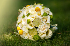 Wedding bouquet from beige roses, cinnamon, a lemon, a lime. On a green grass stock photography
