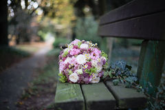 Wedding bouquet on the bench in a park Stock Images