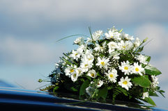 Wedding Bouquet On A Black Car. Wedding bouquet of white and yellow flowers and baby's breath, laying on the hood of a black car stock images