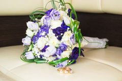 Wedding bouquet with blue flowers and golden rings. Close up Stock Photos