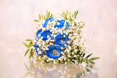 Wedding bouquet of blue and white flowers. Beautiful wedding bouquet of blue and white flowers on the glass table Stock Image
