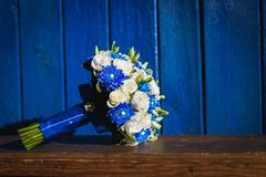 Wedding bouquet with blue and white flowers on a blue background royalty free stock image