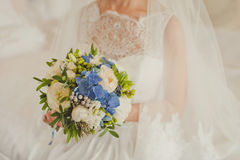 Wedding bouquet. With blue and white flowers in the hands of the bride Stock Images