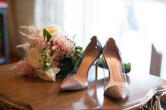 Wedding bouquet and bridal shoes on a table Stock Photography