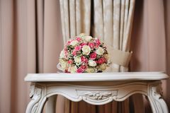 Wedding bouquet of bride - colorful flowers pink, white roses lying on table at wedding Royalty Free Stock Photos