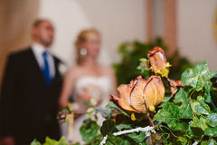 Wedding bouquet with bride and groom in background Royalty Free Stock Photography