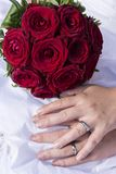 Wedding bouquet. Bride and groom holding hands next to a red wedding bouquet on a white dress stock image