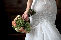 Wedding. Bouquet in bride hand,back view. Bride in white dress on dark background.copy space for text stock photography