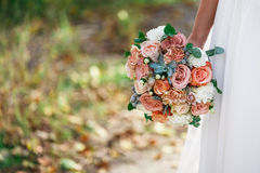 Wedding bouquet in bride hand outdoors Stock Image